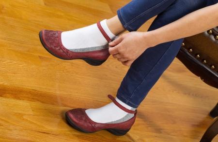 calcetines: Foto horizontal de la mujer ponerse los zapatos causales mientras est� sentado en taburete de cuero acolchado con pisos de roble de color rojo en el fondo Foto de archivo