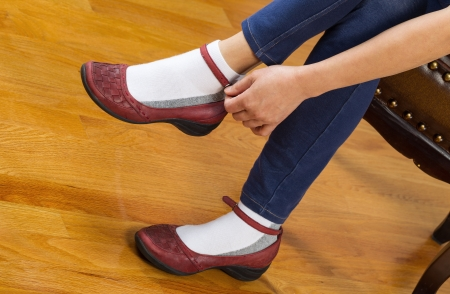 Horizontal photo of woman putting on causal shoes while sitting on leather padded footstool with red oak floors in background