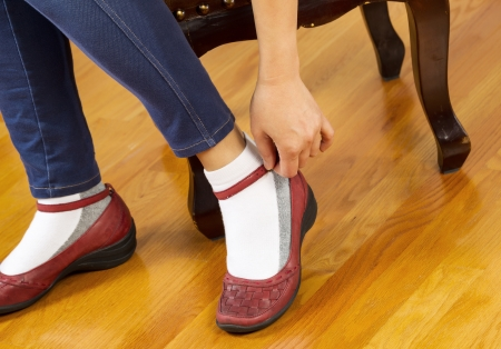 footstool: Horizontal photo of woman snapping strap on causal shoes while sitting on leather padded footstool with red oak floors in background