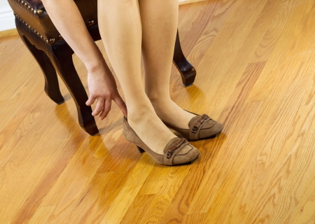 footstool: Horizontal photo of woman, wearing stockings, putting on dress shoes while sitting on leather padded footstool with red oak floors in background  Stock Photo