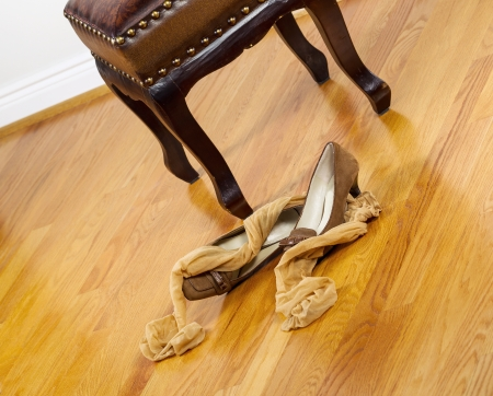footstool: Angled photo of woman stockings and dress shoes lying next to padded footstool with red oak floors in background