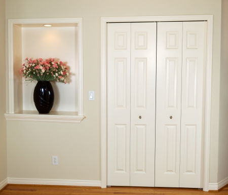 closet door: Interior photo of front closet and wall with decorated flower and light
