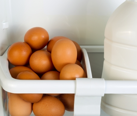 cold storage: Closeup photo of Fresh brown organic eggs and partial milk container on inside of refrigerator door shelf