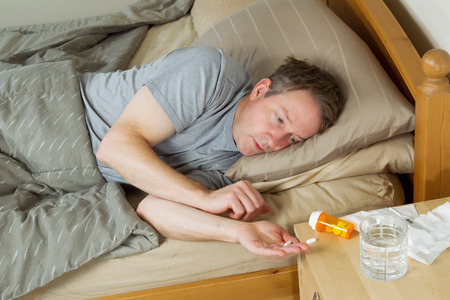 night table: Horizontal photo of mature man putting pill in his hand while lying in bed