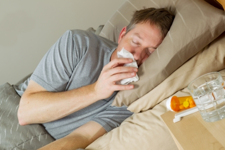 bedridden: Closeup photo of mature man wiping nose with tissue while lying in bed with night stand and medicine in forefront  Stock Photo