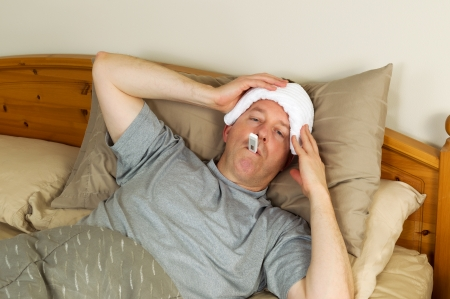 bedridden: Horizontal photo of mature man holding wash cloth to his forehead along with thermometer in mouth while lying in bed