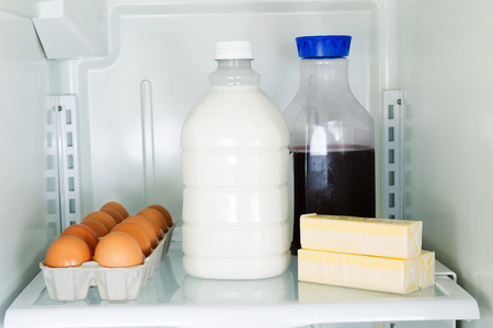 Horizontal photo of milk, eggs, butter and juice on glass shelf inside of refrigerator photo