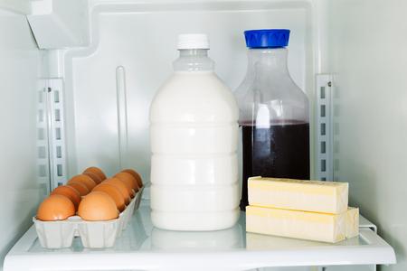 fridge: Horizontal photo of milk, eggs, butter and juice on glass shelf inside of refrigerator