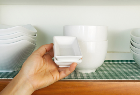 dinnerware: Horizontal photo of female hand putting small square dishes back into kitchen cabinet  Stock Photo