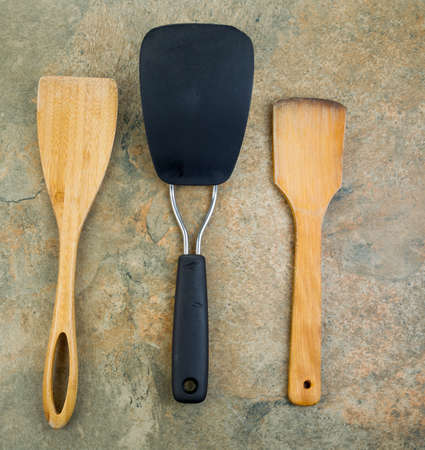 Photo of three kitchen spatulas, two of them wooden, on natural stone Imagens