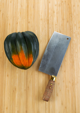 Vertical photo of single large acorn squash with butcher knife on natural bamboo cutting board