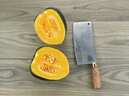 acorn: Photo of large acorn squash cut in half with butcher knife on aging white ash wood