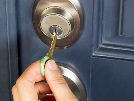 female hand putting house key into front door lock of house Stock Photo