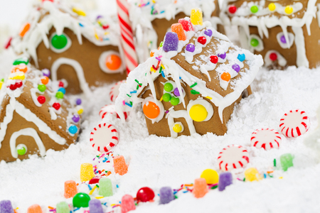 Gingerbread houses surrounded by powered snow and candy cane candies