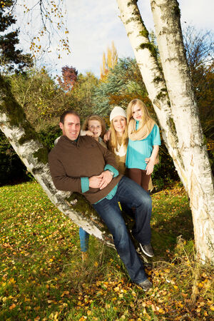 Vertical photo of family resting on trees, with man in forefront, during a lovely day in autumn photo