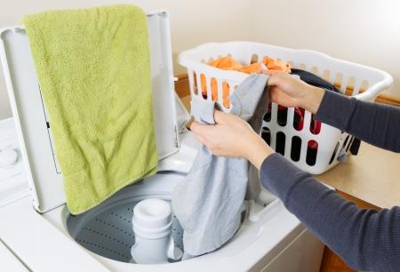 lavadora con ropa: Foto horizontal femeninas manos poniendo la ropa sucia en la lavadora Foto de archivo