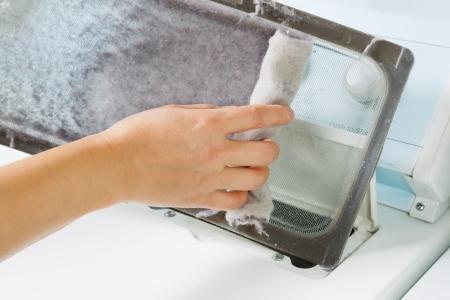여성의 손의 가로 사진은 상기 다이어 기계의 더러운 공기 필터로부터 빌려 복용