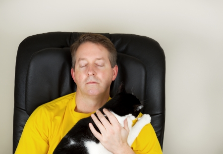 massage chair: Photo of mature man relaxing in massage, with eyes closed, chair while holding a black and white cat Stock Photo