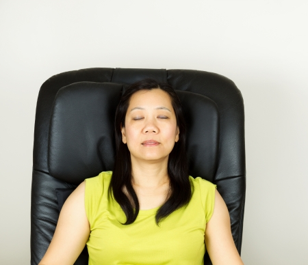 Photo of mature woman relaxing in massage chair, eyes closed, with wall in background