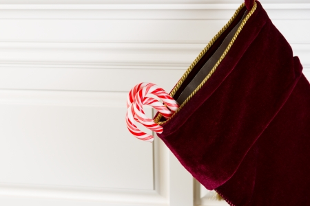 Horizontal photo of Christmas stocking hanging from fireplace mantle with real candy canes hanging outside Imagens - 24209360