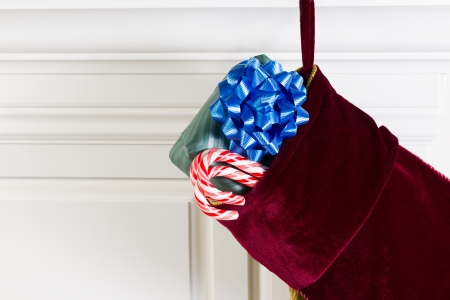 Horizontal photo of Christmas stocking hanging from fireplace mantle with real candy canes and packaged gift hanging outside photo