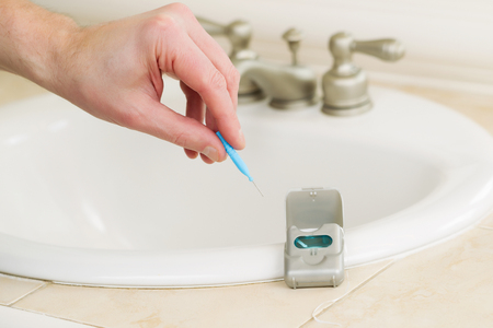 Horizontal photo of male hand picking up dental tooth pick in bathroom with dental floss container, sink and counter top in background  Stock Photo - 24209530