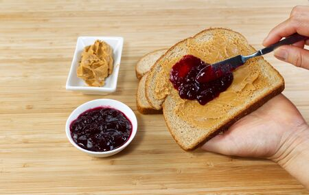 Horizontal photo of female hands making peanut butter and jelly sandwich with natural bamboo cutting board underneath photo