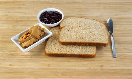 peanut butter and jelly sandwich: Horizontal photo of peanut butter and jelly sandwich ingredients and spread knife with natural bamboo cutting board underneath Stock Photo