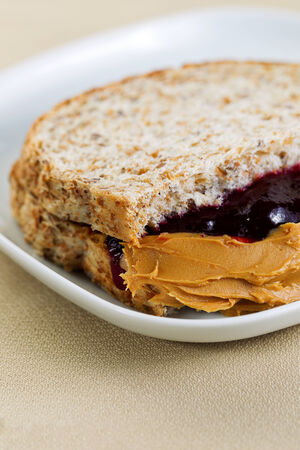 peanut butter and jelly sandwich: Closeup vertical photo of peanut butter and jelly sandwich, cut in half, inside white plate on textured table cloth underneath Stock Photo