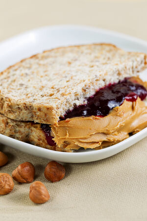 peanut butter and jelly sandwich: Closeup vertical photo of a peanut butter and jelly sandwich cut in half, inside white plate with whole nuts lying on textured table cloth