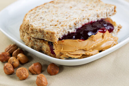 peanut butter and jelly sandwich: Closeup horizontal photo of a peanut butter and jelly sandwich cut in half, inside white plate with whole nuts lying on textured table cloth