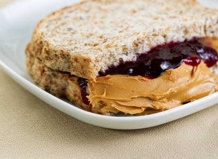Closeup horizontal photo of a peanut butter and jelly sandwich cut in half, inside white plate on textured table cloth underneath photo