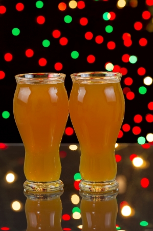 microbrewery: Vertical photo of two tall glasses, on glass table, filled with premium Amber Ale with party lights