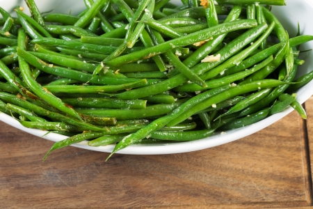 green bean: Horizontal shot of freshly cooked green beans in white bowl on black walnut serving board Stock Photo