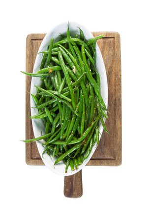 Vertical shot of freshly cooked green beans in white bowl on black walnut serving board isolated on white