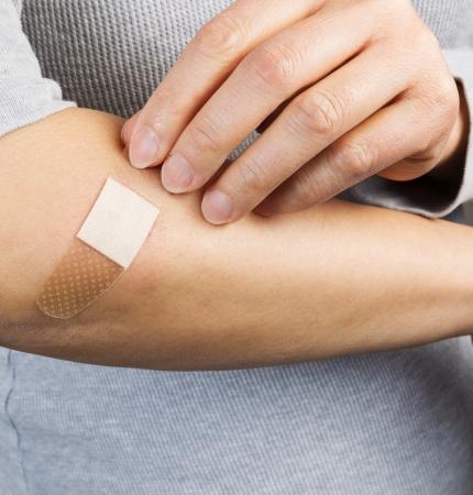 band aid: Photo of female hand putting band aid on cut
