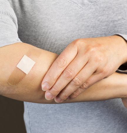 adhesive bandage: Closeup shot of female forearm with bandage covering cut
