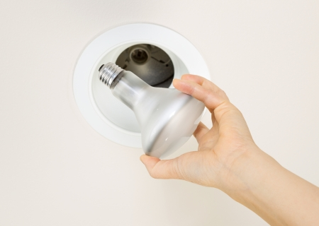 burned out: Photo of burned out flood light bulb being held by female hand with recessed ceiling light mount in background  Stock Photo