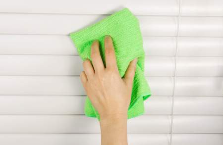 Horizontal photo of female hand cleaning blinds with microfiber cloth Stock Photo