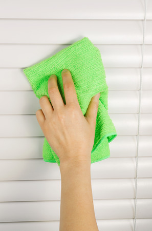 a blind: Vertical photo of female hand cleaning window blinds with microfiber cloth Stock Photo