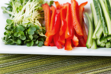 Horizontal closeup photo of freshly sliced red peppers, placed in white plate, along with sliced cucumbers, and daikon radish sprouts with textured table cloth underneath