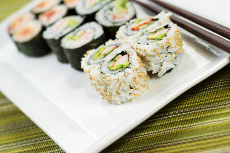 handmade California sushi rolls, filling white plate, and chop sticks in with texture green cloth underneath  版權商用圖片