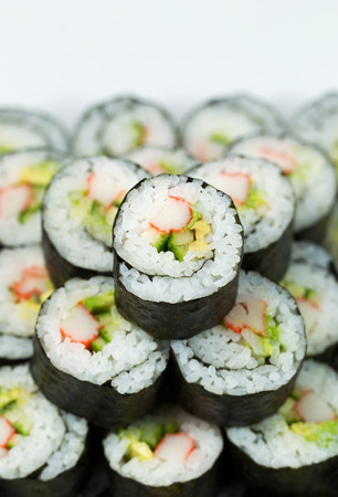 Vertical closeup photo of Single California hand roll sushi on top of pile of additional sushi
