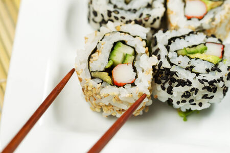 california roll: Closeup horizontal of a single inside out California roll being picked up with chopsticks