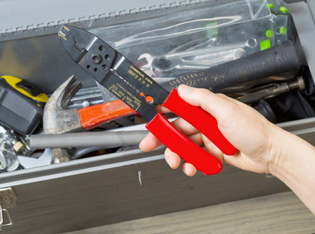wire cutters: Horizontal photo of female hand taking out electrical wire cutters from used toolbox with aged wooden floors underneath