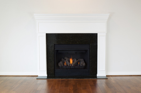 Horizontal photo of a natural gas fireplace with a white mantle and cherry wood floors  Banque d'images