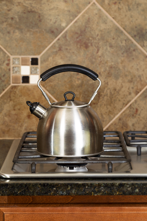 splash back: Vertical photo of a stainless steel tea pot on stove top with stone counter tops and tile back splash  Stock Photo