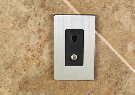 outlets: Horizontal photo of a phone jack and cable outlet on tiled wall