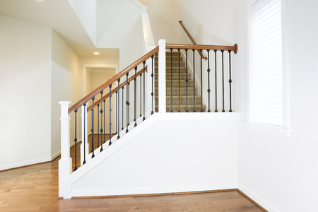 Horizontal photo of residential hard wooden floors and custom staircase made of iron and wood railing with carpet on steps Stock Photo