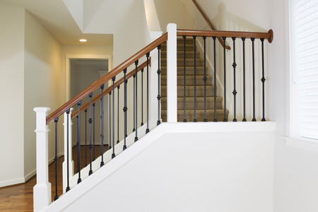 Horizontal photo of residential home staircase made of iron and wood with carpet on steps photo